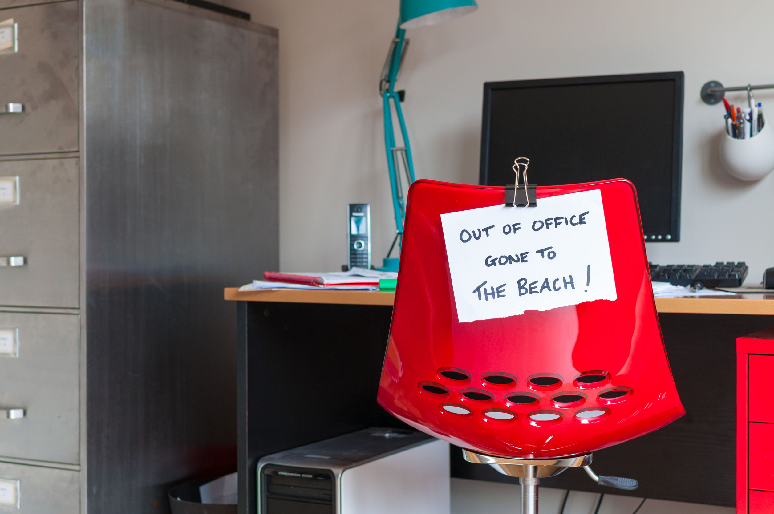 32840853 - Employee Leaves Note On Back Of Office Chair: Out Of Office. Gone To The Beach!